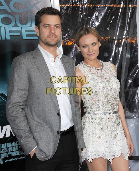 JOSHUA JACKSON & DIANE KRUGER.Premiere of Unknown held at The Regency Village Theatre in Westwood, California, USA..February 16th, 2011      .half length white lace mini dress sleeveless silver belt beads beaded embellished jewel encrusted grey gray suit jacket shirt stubble facial hair couple  .CAP/RKE/DVS.©DVS/RockinExposures/Capital Pictures.