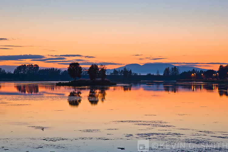 Sunset refleted in the waters of Westchester Lagoon, late summer, Tony Knowles Coastal Trail, Anchorage, Southcentral Alaska, USA.