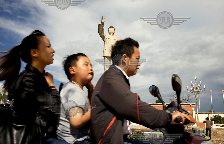 A couple and their child ride, 'three-up', on a motorbike past a huge statue of Chairman Mao that dominates the centre of Lijiang, a town whose historic buildings are a major tourist attraction and an UNESCO World Heritage Site. /Felix Features