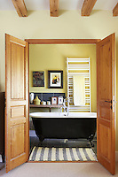 Double doors lead into a cheerful yellow bathroom with a free-standing roll top bath