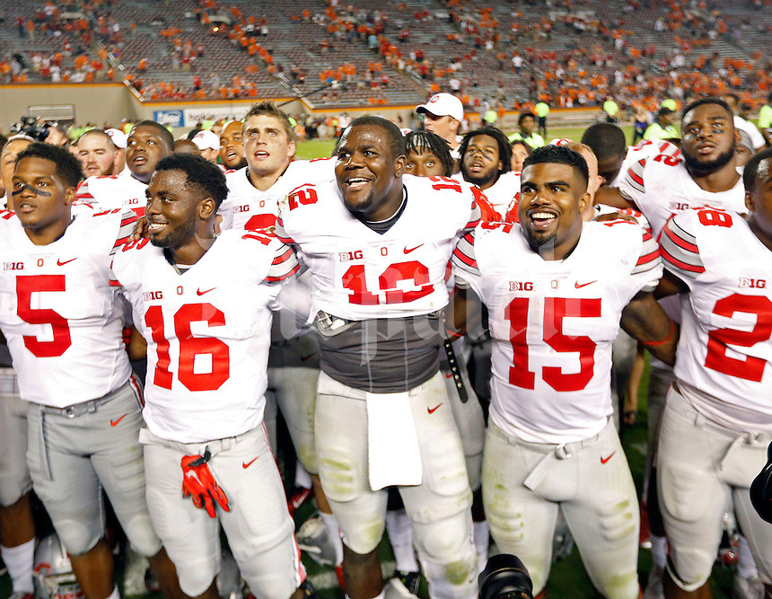 "Ohio State Buckeyes quarterback J.T. Barrett (16), Ohio State Buckeyes quarterback Cardale Jones (12) and Ohio State Buckeyes running back Ezekiel Elliott (15) sing ""Carmen Ohio"" after beating Virginia Tech Hokies 42-24 at Lane Stadium in Blacksburg, Va on September 7, 2015.  (Dispatch photo by Kyle Robertson)"