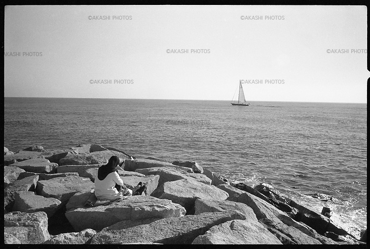 A Muslim woman watches a yacht goes by from the rocks on the beach of Barcelona.
