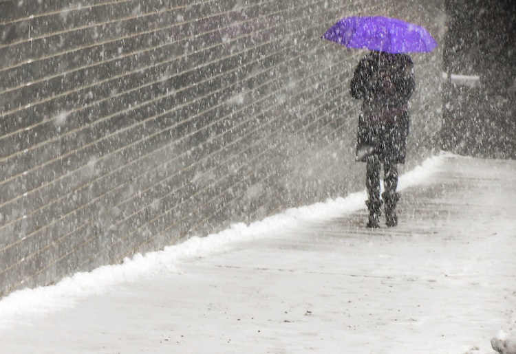 Driving snow as a pedestrian walks down Grand Ave, near Navy Pier. (Photo by Jamie Moncrief)