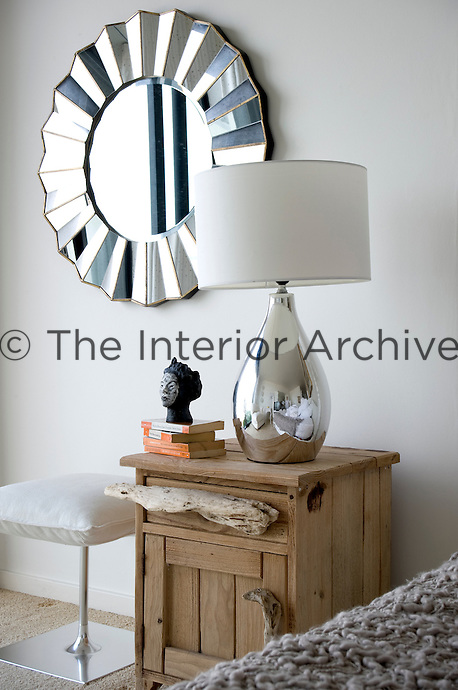 A lamp with a polished metal base stands on top of a bedside locker that has handles fashioned out driftwood