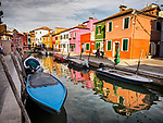A boart in the colorful canal. The colorful village of Burano, Italy.