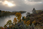 Idaho, Eastern, Swan Valley. Morning sun burns through fog over the South Fork of the Snake River in autumn.