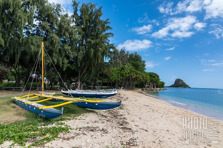 Hawaiian outrigger canoes at Kualoa Regional Park, with Chinaman's Hat in the distance, Kane'ohe Bay, O'ahu.