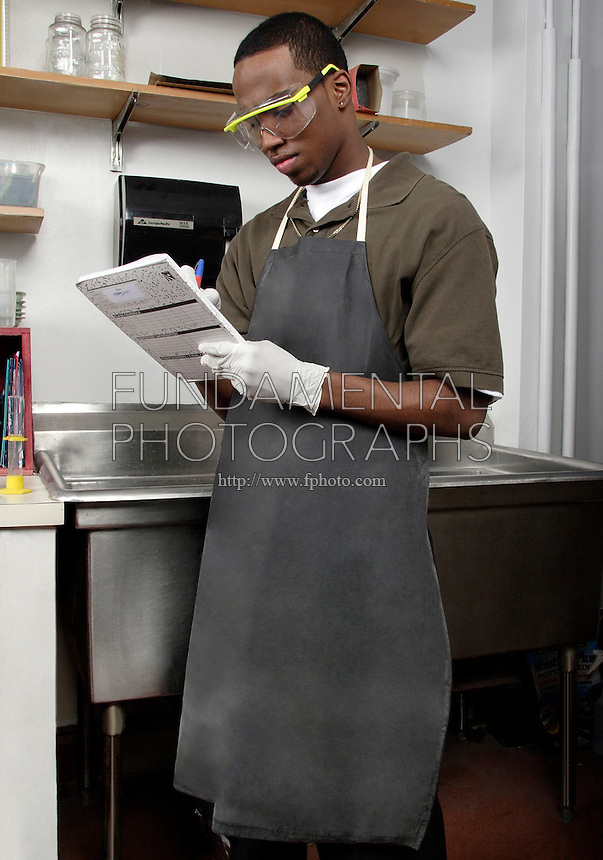 STUDENT WEARING LABORATORY APRON<br /> Protection From Acids and Fluids<br /> Other protective equipment includes goggles and gloves.