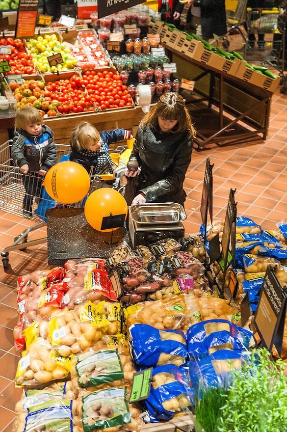 Nederland, Breda, 27 maart 2013.Opening Jumbo Supermarkt..Jumbo heeft vandaag in Breda de deuren geopend van een nieuw supermarktconcept in Nederland: Jumbo Foodmarkt. Met 6.000 vierkante meter vloeroppervlakte - gemiddeld zes keer groter dan de gemiddelde supermarkt - wordt boodschappen doen hier een belevenis. .Klant met twee kinderen in de winkelwagen.Foto(c): Michiel Wijnbergh