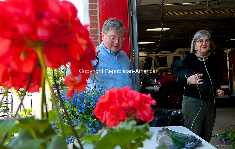 SOUTHBURY,  CT-051217JS03- John and Liz Schmidt of Southbury, look over plants for sale during the annual Mothers Day plant sale hosted by the Southbury Volunteer Fireman's Association's Ladies Auxiliary Friday at the Southbury firehouse. The sale, which benefits local firefighters, children's charities food pantries and the Southbury Needy Fund, will continue today from 9 a.m. to 1 p.m.<br />   Jim Shannon Republican-American