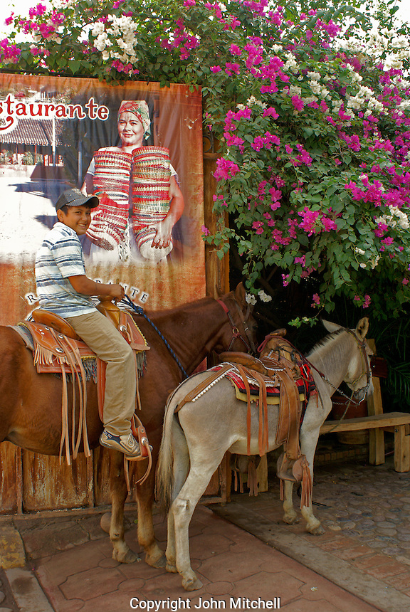 Boy sitting on a horse  in the town of El Quelite near  Mazatlan, Sinaloa, Mexico