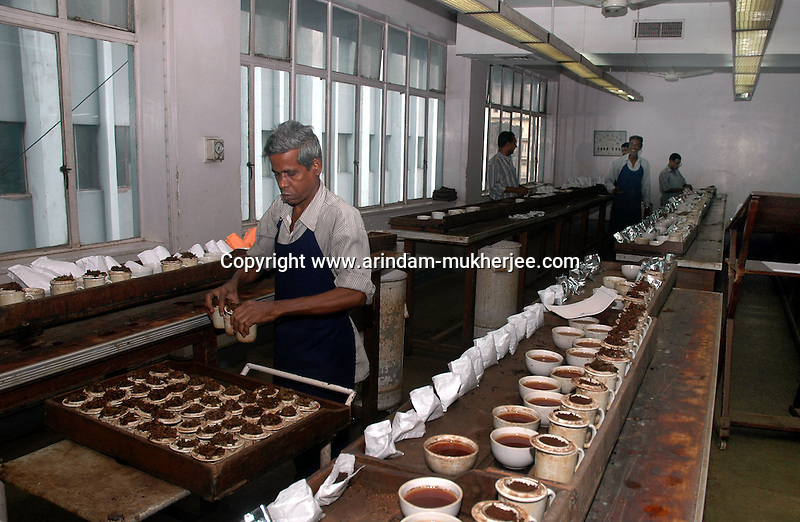 A worker at work in the tea testing room of J. Thomas ltd. company in Kolkata, West Bengal,  India, Arindam Mukherjee