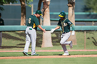 Oakland Athletics first baseman Alfonso Rivas (26) is congratulated by the third base coach after hitting a home run during an Instructional League game against the Los Angeles Dodgers at Camelback Ranch on October 4, 2018 in Glendale, Arizona. (Zachary Lucy/Four Seam Images)