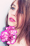 Young girl with brown hair make up and pale skin, looking nervously over her shoulder with carnations held in her hand