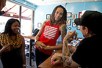 Jun. 10, 2013; Phoenix, AZ, USA: Phoenix Mercury center Brittney Griner (center) with her girlfriend inside the Golden Rule Tattoo shop in downtown Phoenix. Mandatory Credit: Mark J. Rebilas-
