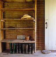Pairs of muddy Wellington boots are lined up under a rustic and rudimentary wooden shelving unit