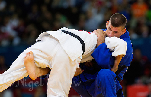 29 JUL 2012 - LONDON, GBR - Miklos Ungvari (HUN) (in blue)  of Hungary tries to overpower Sugoi Uriarte (ESP) of Spain during their  men's -66kg category semi final at the London 2012 Olympic Games judo at the ExCel Exhibition Centre in London, Great Britain .(PHOTO (C) 2012 NIGEL FARROW)