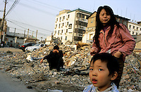 CHINA. Beijing. A family stand in the ruins of an old hutong (traditional home) in the central Qianmen district, destroyed to make may for new developments aimed at modernising the city for the 2008 Summer Olympics. 2005