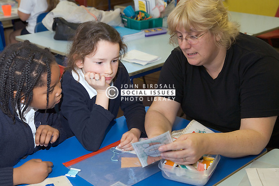 Teacher showing primary school pupils how to sew during a needlework lesson at school,