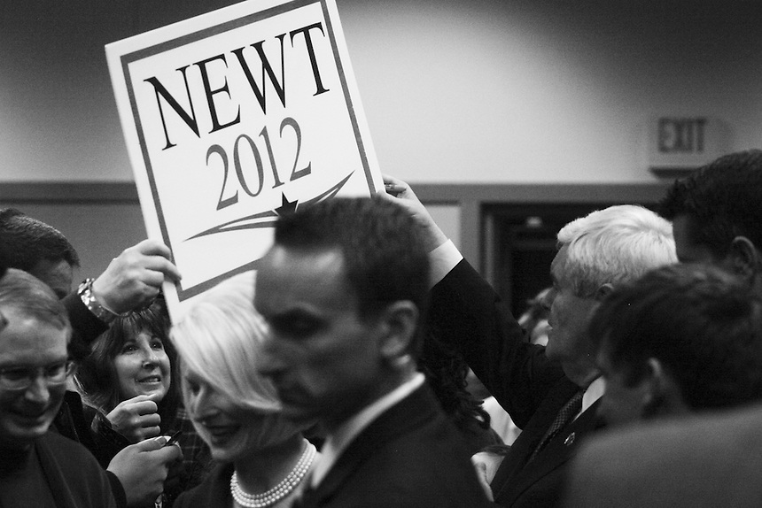 Newt Gingrich grabs a sign from a supporter in the conference room at the Best Western Plus in Couer d'Alene, Idaho on Thursday, February 23.