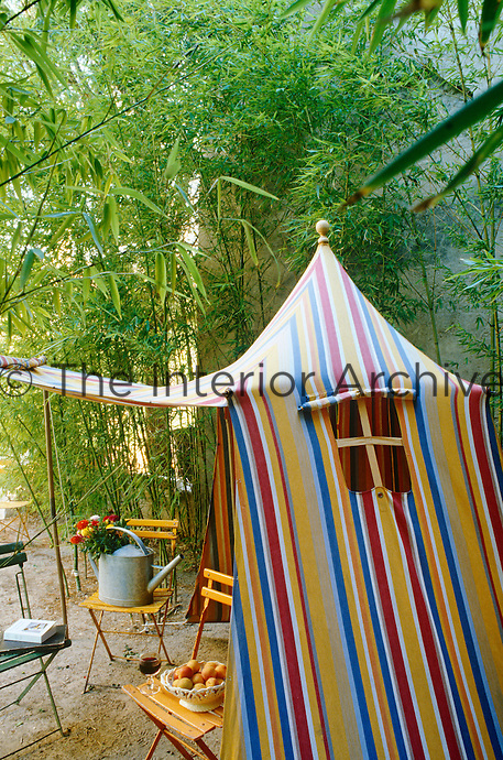 A 19th century tent in multi-coloured stripes and a collection of folding garden chairs are arranged in a grove of bamboo