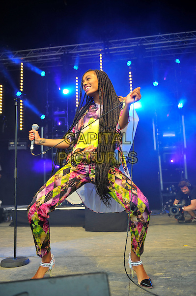 Solange (Solange Knowles) <br /> performing at Glastonbury Festival, Worthy Farm, Pilton, Somerset, <br /> England, UK, 28th June 2013.<br /> full length music gig concert gig live on stage microphone  long hair braids smiling dancing  pink yellow white print catsuit jumpsuit top bending legs <br /> CAP/MAR<br /> &copy; Martin Harris/Capital Pictures