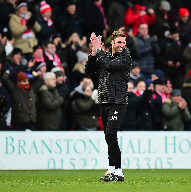 Lincoln City's first team coach/under 23 manager Jamie McCombe applauds the fans at the final whistle<br /> <br /> Photographer Andrew Vaughan/CameraSport<br /> <br /> The EFL Sky Bet League Two - Lincoln City v Grimsby Town - Saturday 19 January 2019 - Sincil Bank - Lincoln<br /> <br /> World Copyright &copy; 2019 CameraSport. All rights reserved. 43 Linden Ave. Countesthorpe. Leicester. England. LE8 5PG - Tel: +44 (0) 116 277 4147 - admin@camerasport.com - www.camerasport.com