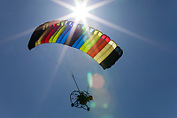 Colorful Powered Parachute in Flight Backlit by the Sun, Arlington, WA, USA.