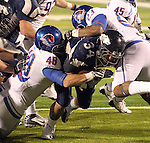 Nevada Wolf Pack running back Vai Taua pushes through the Boise State Broncos defense to score during the NCAA college football game Saturday night, Nov. 26, 2010, in Reno, Nev. (AP Photo/Cathleen Allison)