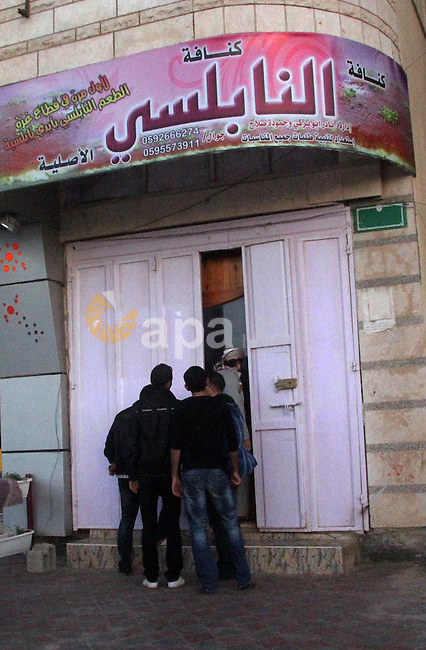 Palestinians gather at the entrance of sweet store of Palestinian former prisoners Hamouda Salah and Radwan Abu Turki, in Gaza city on March 29, 2013. Salah and Abu Turki was released by Israel as part of the Gilad Shalit prisoner exchange agreement and banished from the West Bank city of Hebron to Gaza City. Photo by Ezz al-Zanoon
