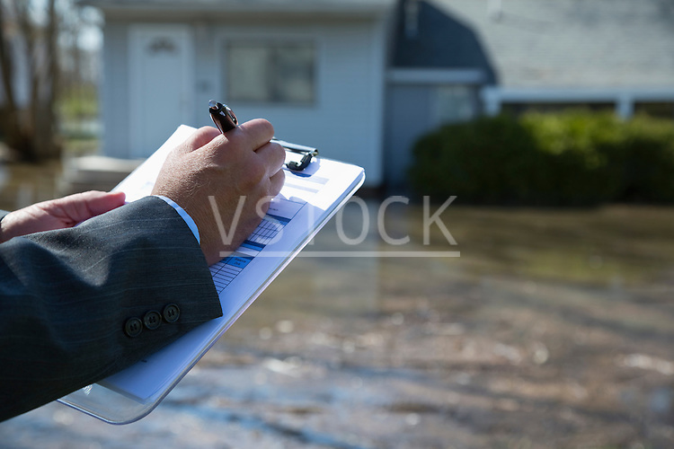 Claim auditor filling chart in flooded town