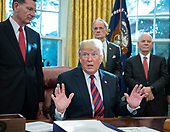 United States President Donald J. Trump speaks to the press pool after signing S.3021, America's Water Infrastructure Act of 2018 in the Oval Office of the White House in Washington, DC on Tuesday, October 23, 2018.  The President took questions from the pool on the caravan and Saudi Arabia.  Looking on from left are: US Senator John Barrasso (Republican of Wyoming), US Senator Tom Carper (Democrat of Delaware), US Senator Ben Cardin (Democrat of Maryland).<br /> Credit: Ron Sachs / Pool via CNP