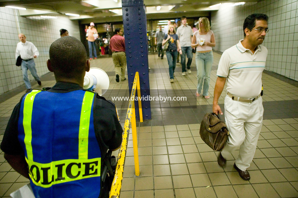 22 July 2005 - New York City, USA - Police officer Russel King (2L) informs travellers that they may be required to submit to a bag search as they enter the 42 St Port Authority Bus Terminal subway station, 22 July 2005, New York City, USA. The NYPD decided to subject riders to random bag inspections following the second attack on London's transit system in two weeks. Photo Credit: David Brabyn.