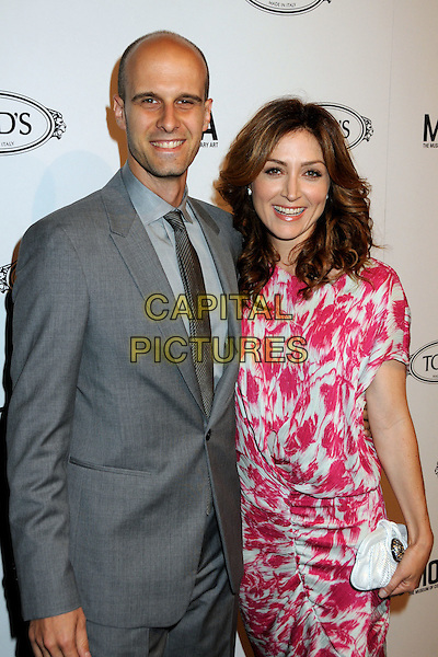 EDOARDO PONTI & SASHA ALEXANDER .TOD's Beverly Hills Boutique Launch Celebration held at TOD's Boutique, Beverly Hills, California, USA, .15th April 2010..Half length pink  print dress white  clutch bag ruched grey gray suit tie smiling .CAP/ADM/BP.©Byron Purvis/AdMedia/Capital Pictures.