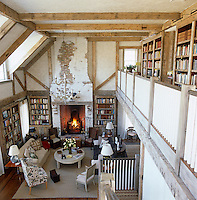 The library/sitting room in this converted barn benefits from a double height ceiling