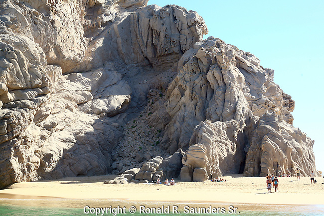 Tourists dwarfed by large rock formation at Divorce Beach