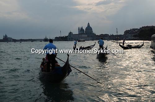 Venice Italy 2009. Tourists gondola rides. The church of Santa Maria della Salute in background.