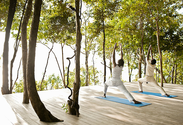 Two Men Practicing Yoga Outdoors at Six Senses Hideaway Yao Noi, Koh Yao Noi, Thailand. A yoga instructor gives a private yoga lesson on the treetop platform overlooking Phang Nga Bay at Six Senses Hideaway Yao Noi.