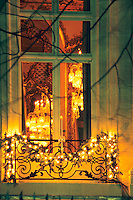 Outside looking in, through a window the crystal candelabra and chandeliers, wrought iron railing with Christmas decorations. At The Baccarat museum, shop, restaurant at the Hotel de Noailles in Paris. Designed by Philippe Starck. The Baccarat Museum: from the outside you can see the chandelier, the gilled and sculptured ceilings....