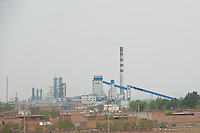 Daytime horizontal view from a train of a smokestack at a commercial manufacturing facility near Píngyáo county of the Jìnzhōng District in Shānxī Province, China  © LAN