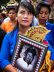 16 JULY 2016 - UBUD, BALI, INDONESIA:  A woman holds a picture of a man being cremated during the mass cremation in Ubud. Local people in Ubud exhumed the remains of family members and burned their remains in a mass cremation ceremony Wednesday. Almost 100 people were cremated and laid to rest in the largest mass cremation in Bali in years this week. Most of the people on Bali are Hindus. Traditional cremations in Bali are very expensive, so communities usually hold one mass cremation approximately every five years. The cremation in Ubud concluded Saturday, with a large community ceremony.    PHOTO BY JACK KURTZ