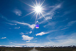 SR 305 in the Reese River Valley of central Nevada, winter day with few clouds; sunburst.
