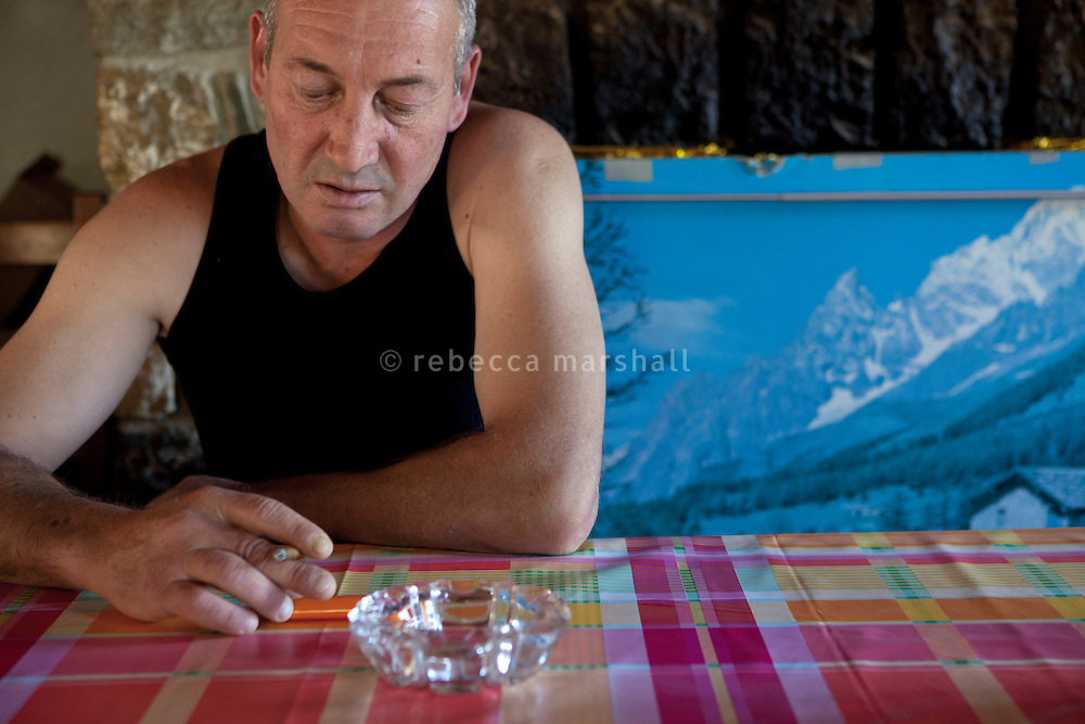Denis Rogeri, sheep-raiser, sits at the table at home, La Bollène Vésubie, Alpes-Maritimes, France, 02 August 2013. Denis, 52 years old, has been raising sheep and pasturing them in the mountains over the summer, since 1988. He and his wife Eliane used to have 1000 sheep, but have now cut the herd down to 700, as management of the large herd with the threat of wolves has become increasingly hard. They lost around 30 sheep to wolf attacks last year alone.