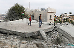 Palestinian youths inspect the rubble of the home of Mohammed Abed Almajid El-Amaira, a Palestinian accused of involvement in a shooting attack that led to the death of a rabbi, after it was destroyed by Israeli military on August 30, 2016 in the West Bank village of Dura near Hebron. Israel frequently destroys the homes of Palestinians who have carried out attacks. Amaira, a member of the Palestinian Authority security services, was arrested several weeks ago, accused of having helped plan and carry out the attack on July 1, when gunmen opened fire on a car near Hebron. The car crashed, killing rabbi Michael Mark, who led a religious school in the Israeli settlement of Otniel, and wounding two family members, according to the army. Photo by Wisam Hashlamoun