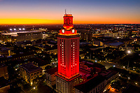 University of Texas Tower lit with Number 1 bright Orange Tower over looking the Darrell K Royal–Texas Memorial Stadium on the UT campus during beautiful Austin sunrise.