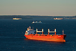 Cargo ships waiting in Puget Sound to off load containers sunrise with Ferry boat