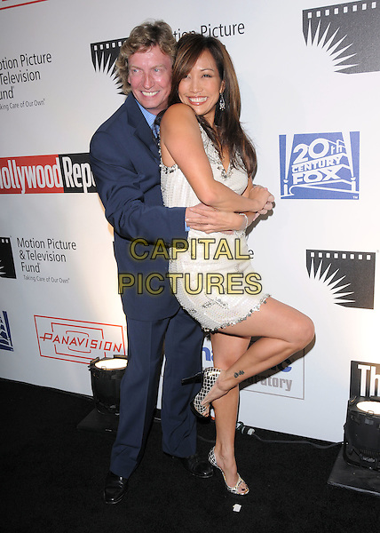 "NIGEL LYTHGOE & CARRIE ANN INABA .at The 4th Annual ""A Fine Romance"" held at Sony Picture Studios in Culver City, California, USA,  .November 08 2008.                                                                     .Full length white dress dancing pose funny sequined cross motif beaded  gold croc shoes platforms shiny black heels blue suit .CAP/DVS.©Debbie VanStory/Capital Pictures"