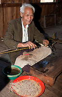 Myanmar, Burma.  Man Weaving with Fiber from Lotus Stems, Inle Lake, Shan State.