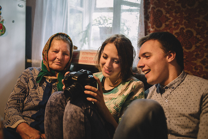 Katrine showing pictures to her grandmother  and Alexander pictures that she took during the celebration of Easter for Dead. Ghidirim, Transnistria
