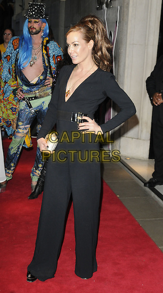 TARA PALMER-TOMKINSON.Freddie For A Day charity gala arrivals, Savoy hotel, the Strand, London, England..September 5th, 2011.full length black jumpsuit plunging neckline costume tpt silver gold clutch bag hand on hip.CAP/CAN.©Can Nguyen/Capital Pictures.